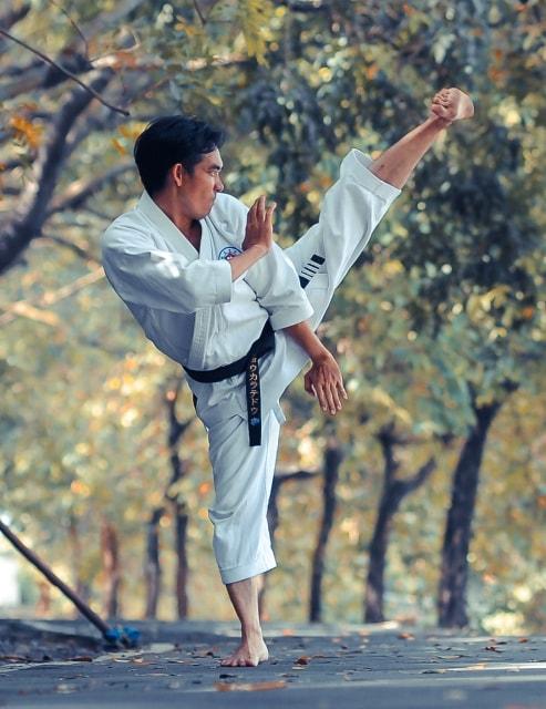 屋外で左足を高く蹴り上げる男性
