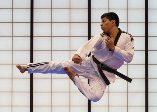 右手を伸ばして飛び蹴りを放つ男性