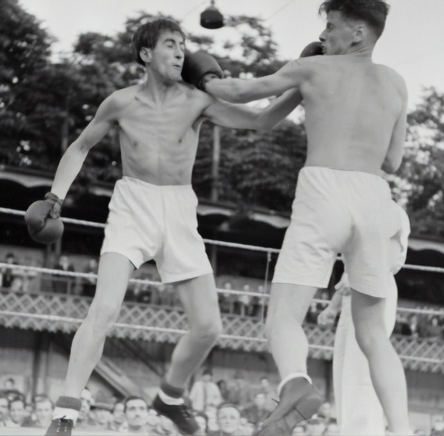 ボクシングの試合で対戦相手の顔にパンチを打つ男性