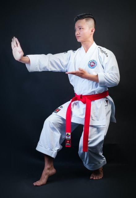 右手を伸ばして拳法の構えの姿勢をとる男性