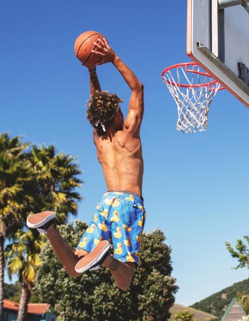バスケットでダンクシュートを放つ男性