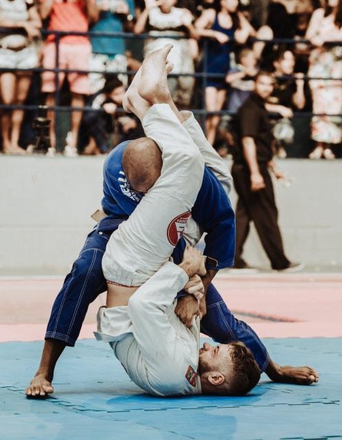 柔道の試合で逆さの姿勢から技をかける男性