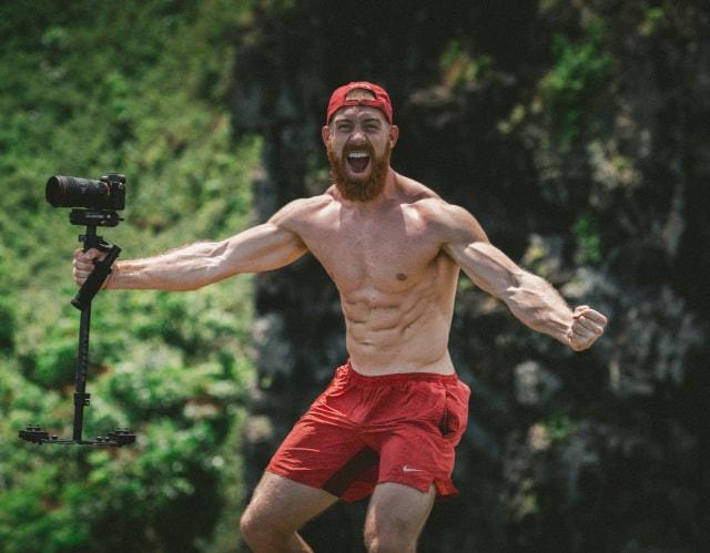 カメラの一脚を掴みながらガッツポーズをとる男性